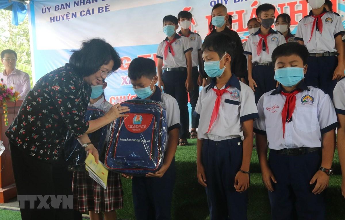 Phó Chủ tịch Nước Đặng Thị Ngọc Thịnh trao quà và học bổng cho học sinh có hoàn cảnh đặc biệt khó khăn xã Hậu Mỹ Bắc B. (Ảnh: Minh Trí/TTXVN)