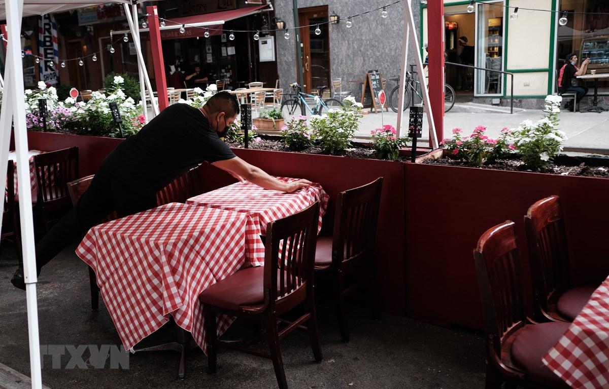Nhân viên sửa soạn lại bàn ghế tại một nhà hàng ở New York, Mỹ. (Ảnh: AFP/TTXVN)