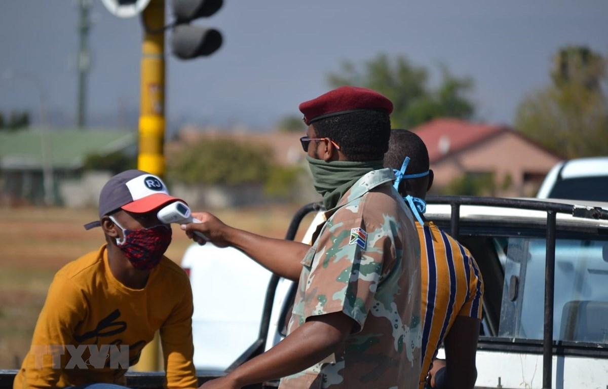 Binh lính Nam Phi kiểm tra thân nhiệt cho một người dân tại ngoại ô thủ đô Pretoria, Nam Phi. (Ảnh: Phi Hùng/TTXVN)