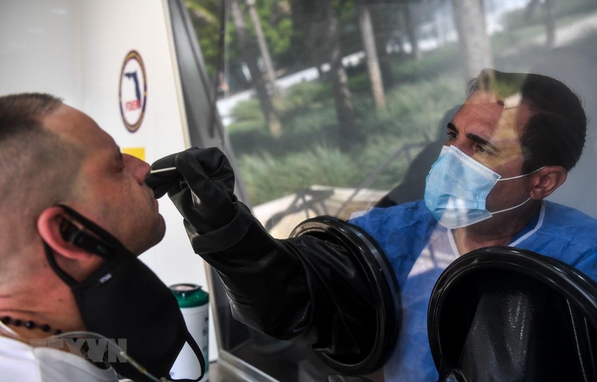 Nhân viên y tế lấy mẫu dịch xét nghiệm COVID-19 cho người dân tại Miami, Mỹ. (Ảnh: AFP/TTXVN)