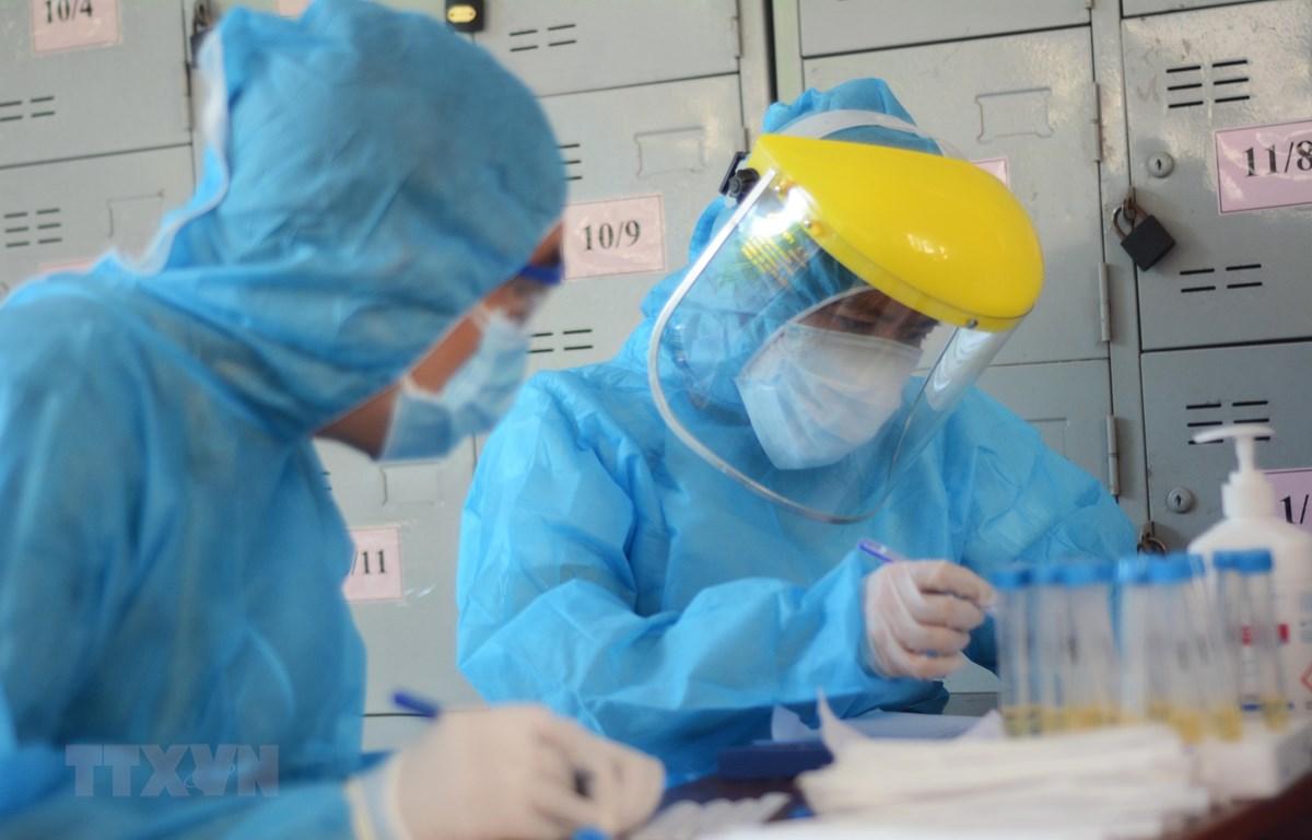 Các nhân viên y tế làm xét nghiệm SARS-CoV-2. (Ảnh: Văn Dũng/TTXVN)