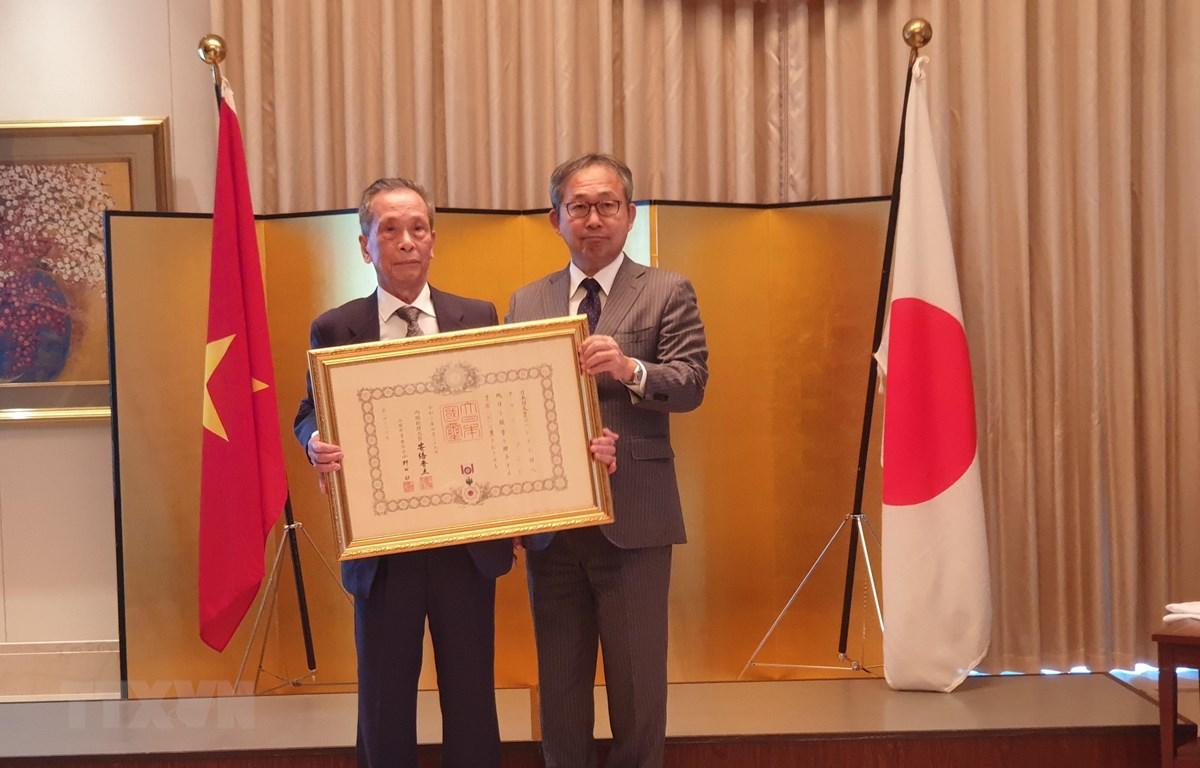Đại sứ Nhật Bản tại Việt Nam trao Huân chương mặt trời mọc tia sáng vàng và nơ thắt hoa hồng cho Phó Giáo sư-Tiến sỹ Trần Sơn. (Ảnh: Phương Anh/TTXVN)