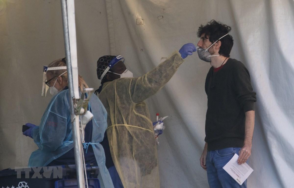 Nhân viên y tế lấy mẫu dịch xét nghiệm COVID-19 cho người dân Mỹ. (Ảnh: THX/TTXVN)