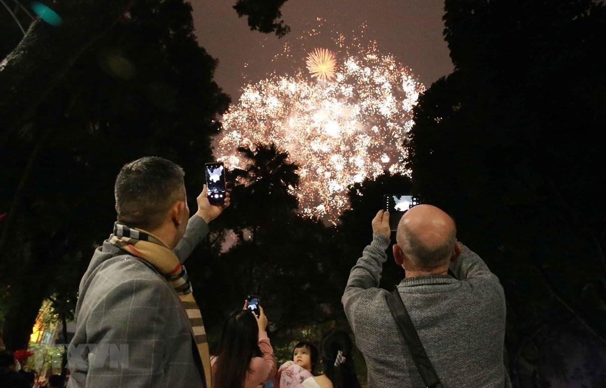 Khách du lịch xem bắn pháo hoa tại hồ Hoàn Kiếm. (Ảnh: Doãn Tấn/TTXVN)