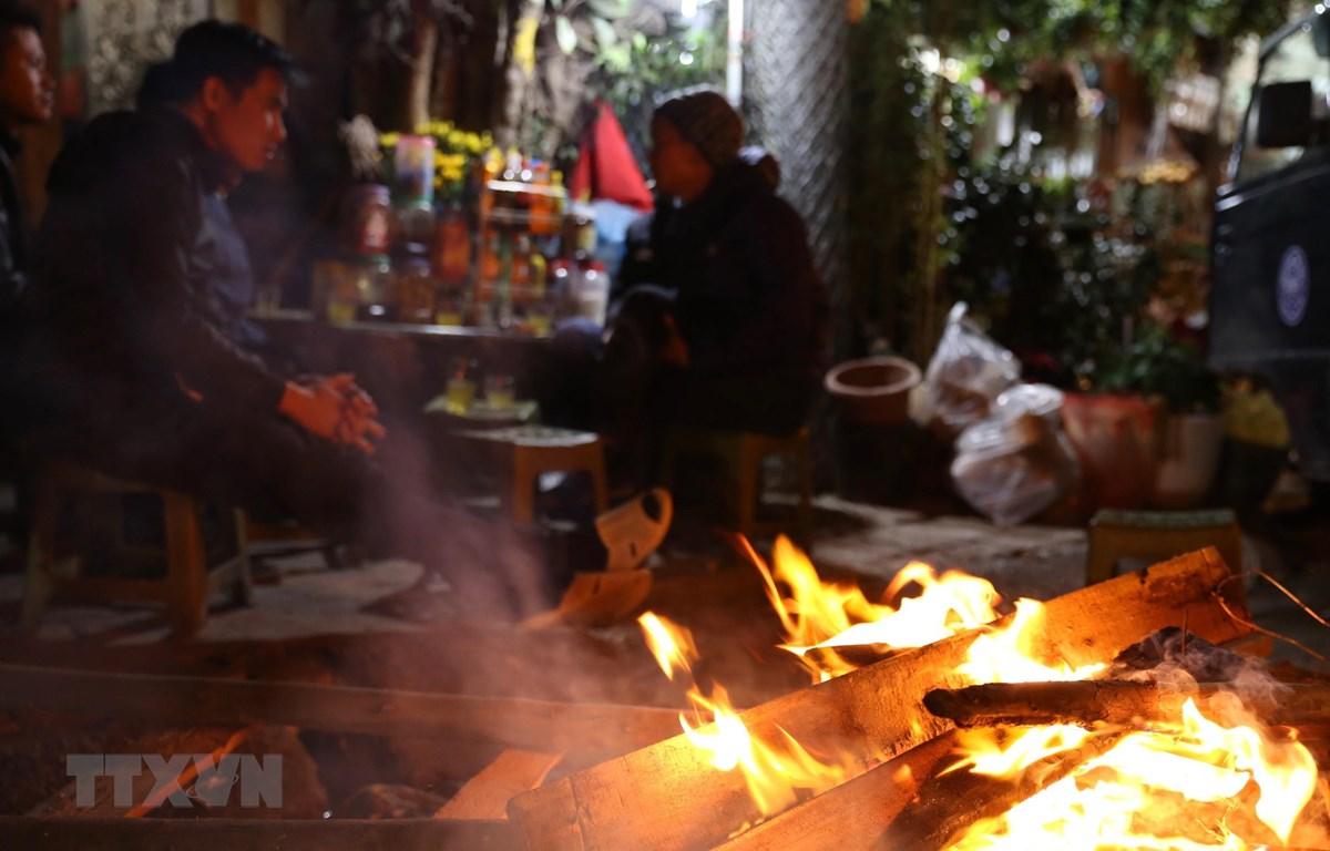 Người dân đốt lửa sưởi ấm trên phố Kim Ngưu, Hà Nội. (Ảnh: Hoàng Hiếu/TTXVN)
