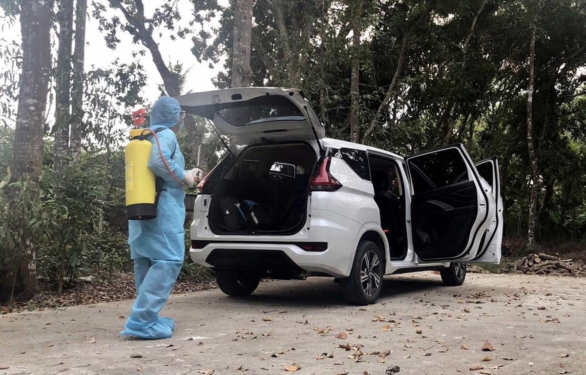 Khử khuẩn xe do tài xế M.T.T chở khách về Sóc Trăng. (Ảnh: TTXVN phát)