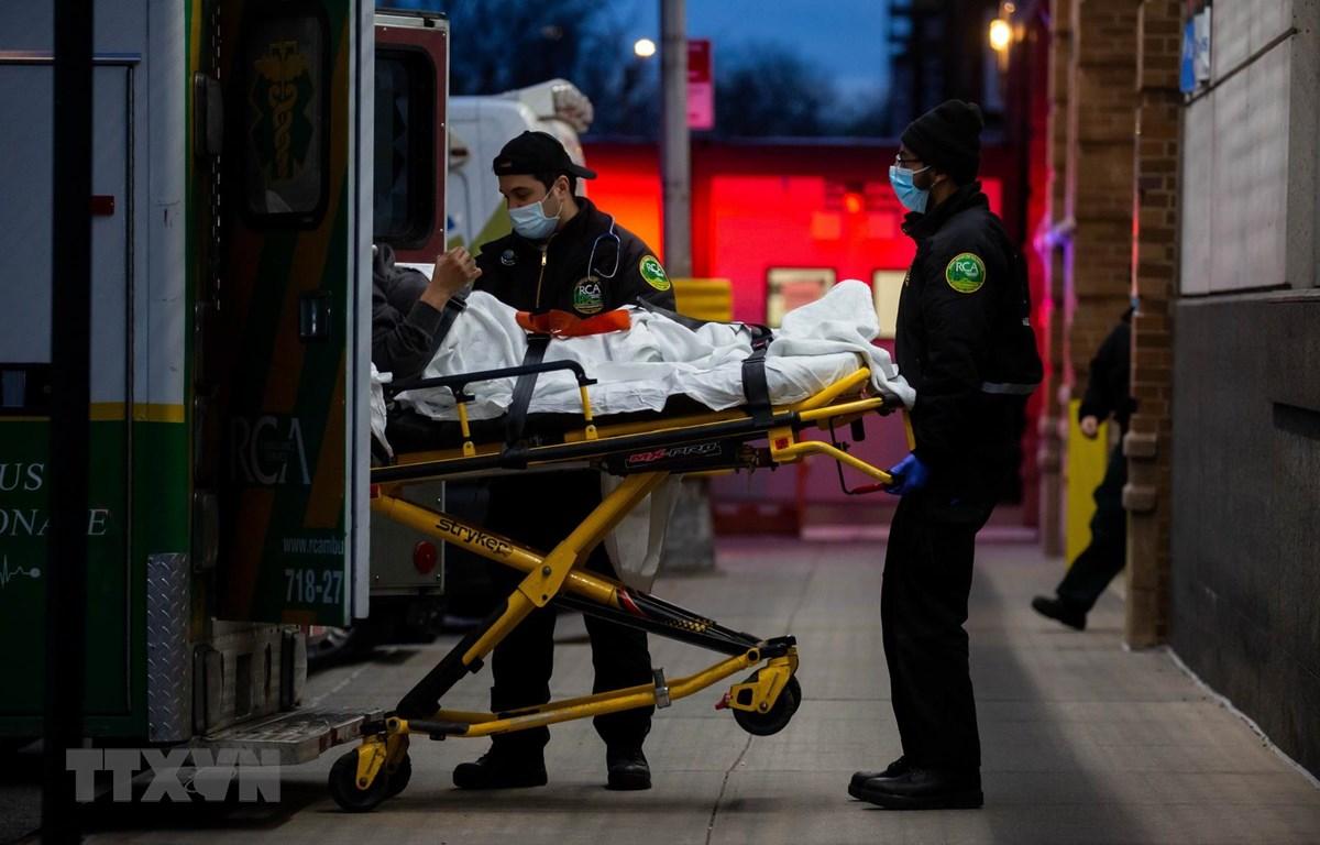 Nhân viên y tế chuyển bệnh nhân COVID-19 tới trung tâm y tế ở New York, Mỹ. (Ảnh: THX/TTXVN)