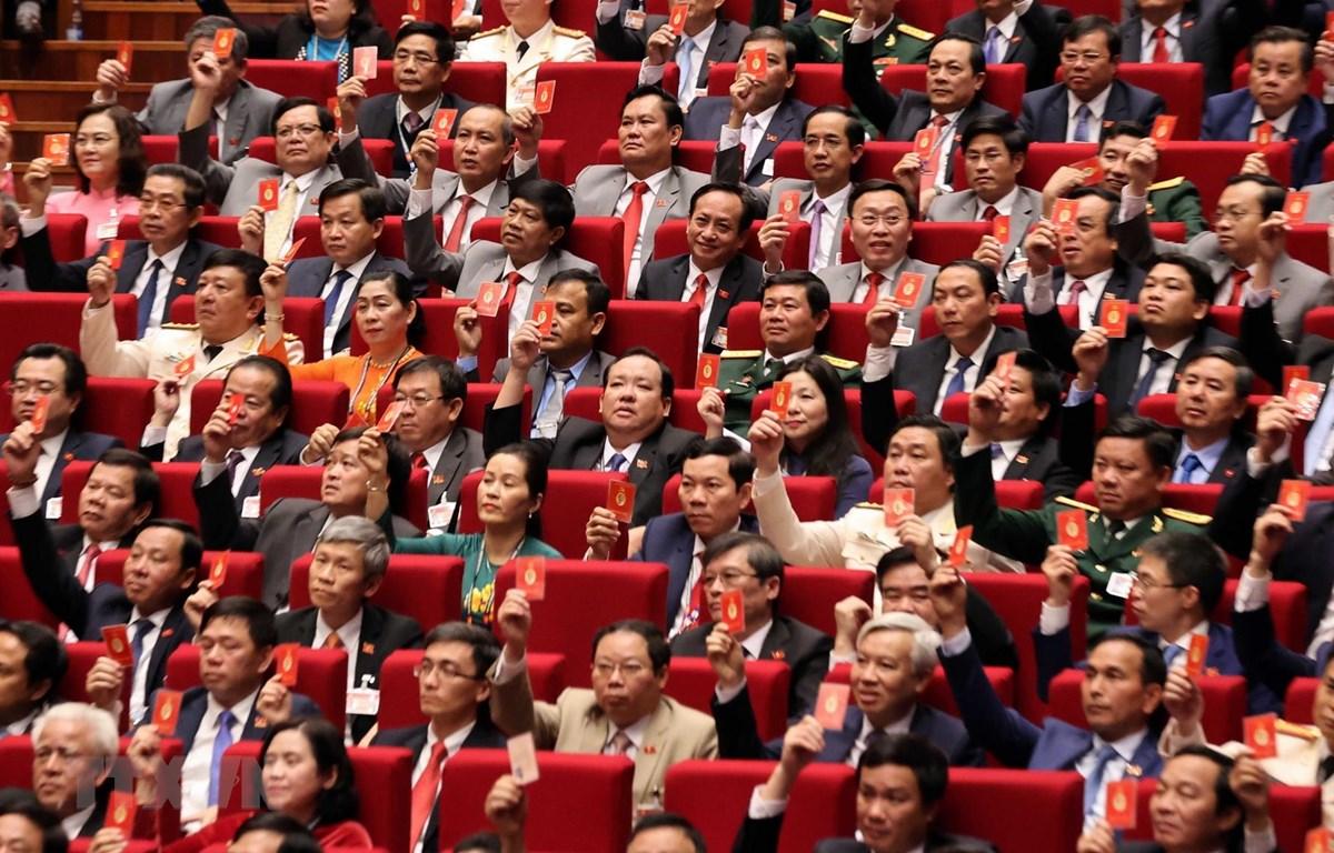 Các đại biểu biểu quyết, thông qua Nghị quyết Đại hội XIII Đảng Cộng sản Việt Nam. (Ảnh: TTXVN)