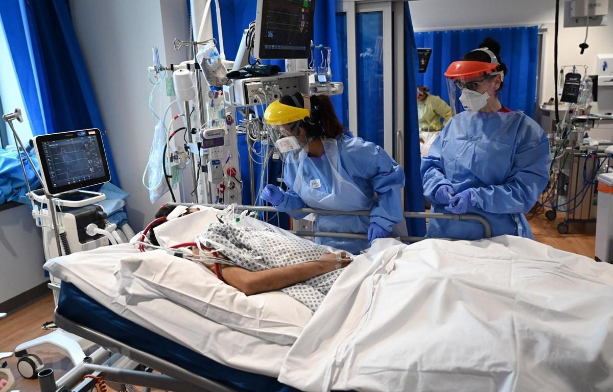 Nhân viên y tế điều trị cho bệnh nhân COVID-19 tại bệnh viện ở Cambridge, Anh. (Ảnh: AFP/TTXVN)