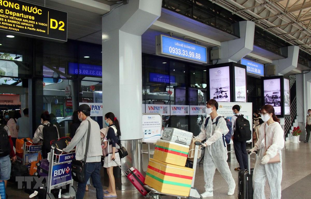 Để phòng chống dịch, nhiều hành khách đã chủ động trang bị các bộ đồ bảo hộ khi đến sân bay Tân Sơn Nhất. (Ảnh: Tiến Lực/TTXVN)