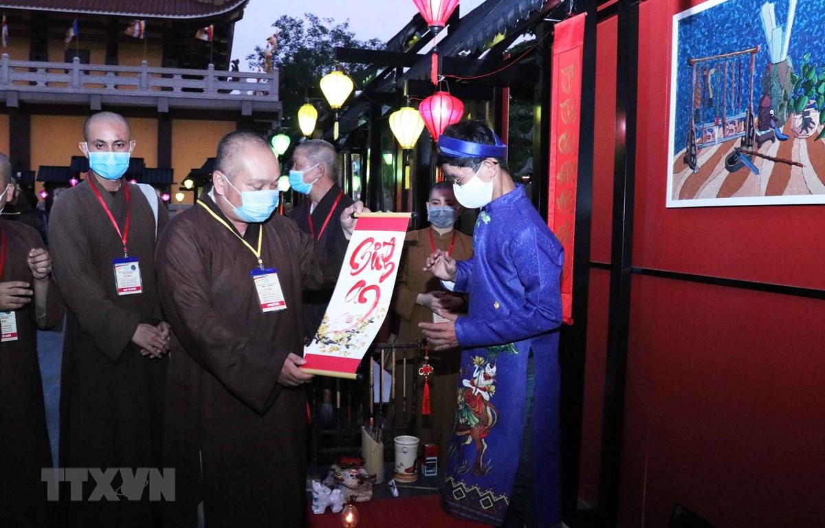 Các chư tăng tham quan, xin chữ ông đồ tại lễ hội Phố ông Đồ 'Xuân bình an.' (Ảnh: Xuân Khu/TTXVN)