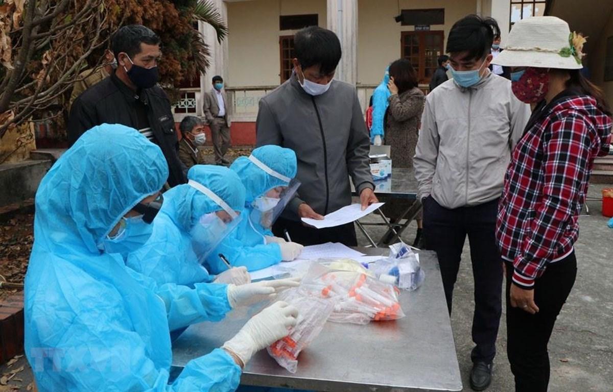 Lấy mẫu xét nghiệm SARS-CoV-2 cho người dân tại xã Hưng Đạo, thành phố Chí Linh chiều 28/1. (Ảnh: Mạnh Minh- TTXVN)