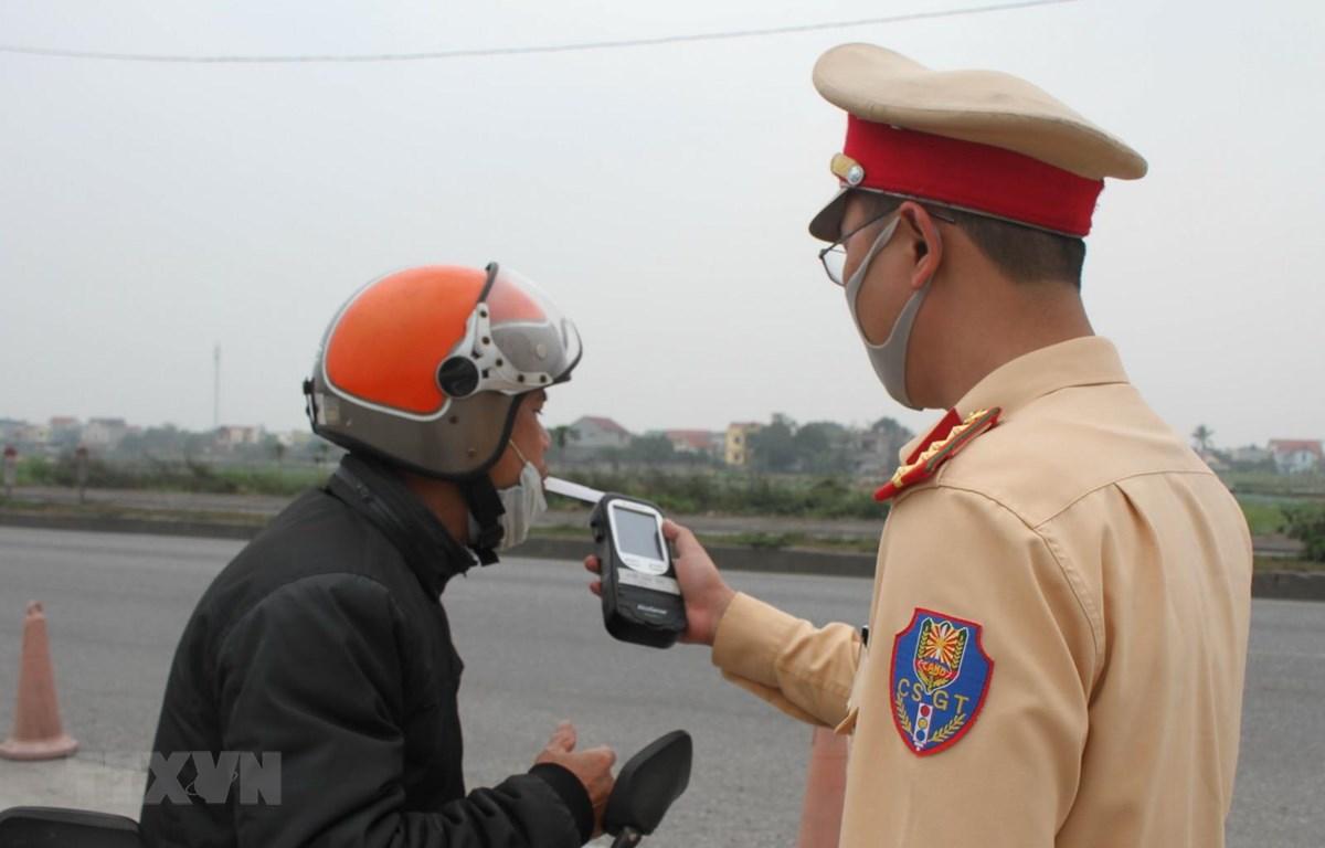Cảnh sát giao thông kiểm tra nồng độ cồn của người điều khiển phương tiện. Ảnh: Thùy Dung/TTXVN