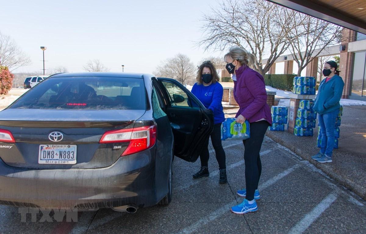 Tình nguyện viên phát nước sạch cho người dân tại Dallas, bang Texas, Mỹ ngày 20/2/2021. (Ảnh: THX/TTXVN)