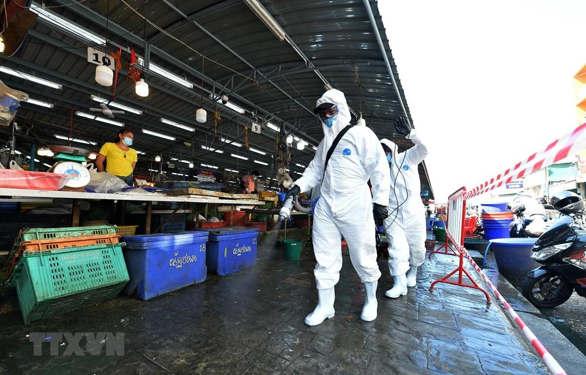 Nhân viên khử khuẩn nhằm ngăn dịch COVID-19 lây lan tại một khu chợ ở tỉnh Samut Sakhon, Thái Lan. (Ảnh: THX/TTXVN)