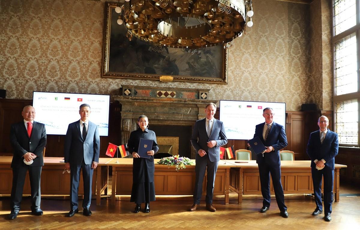Đại diện Tập đoàn Aone Deutschland AG của Đức và Công ty Cổ phần nước AquaOne của Việt Nam ký thỏa thuận khung xây dựng Nhà máy nước mặt sông Vàm Cỏ Đông tại Long An. (Ảnh: Mạnh Hùng/TTXVN)