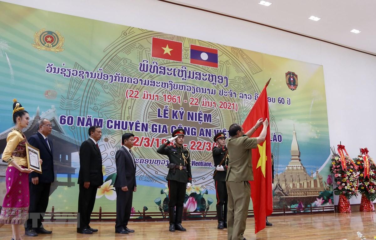 Thượng tướng Vilay Lakhamphong, Bộ trưởng Bộ Công an Lào gắn Huân chương Itsala Hạng II của Đảng Nhà nước Lào cho Cơ quan Đại diện Bộ Công Việt Nam tại Lào. (Ảnh: Phạm Kiên/TTXVN)