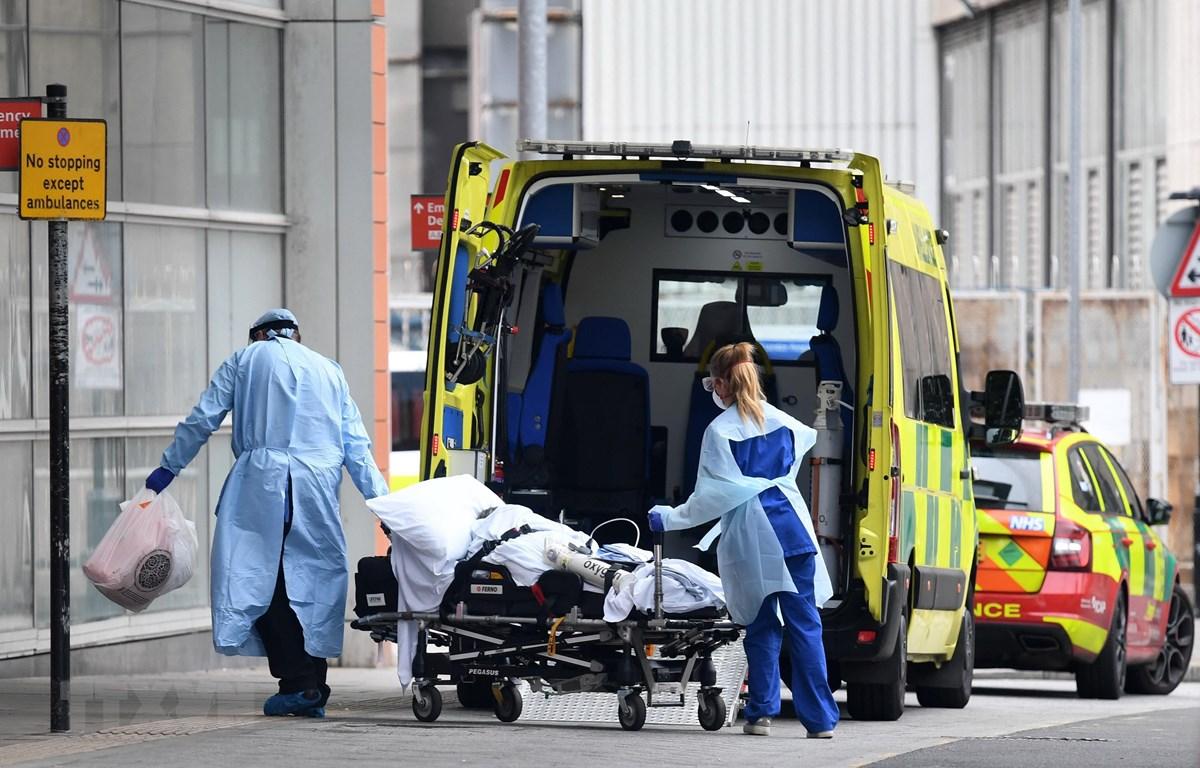 Nhân viên y tế chuyển bệnh nhân COVID-19 tới bệnh viện ở London, Anh. (Ảnh: AFP/TTXVN)