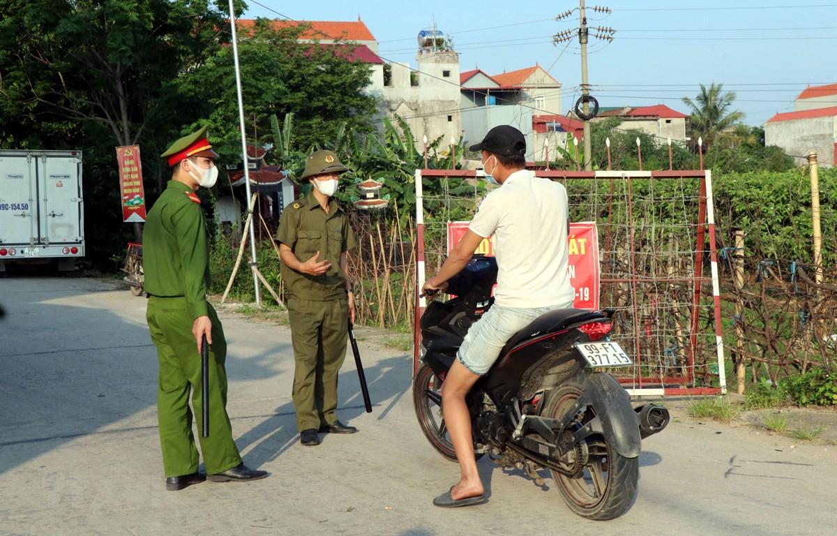 Lực lượng chức năng chốt chặn các lối ra vào tại xã Mão Điền, huyện Thuận Thành, tỉnh Bắc Ninh. (Ảnh: Đinh Văn Nhiều/TTXVN)