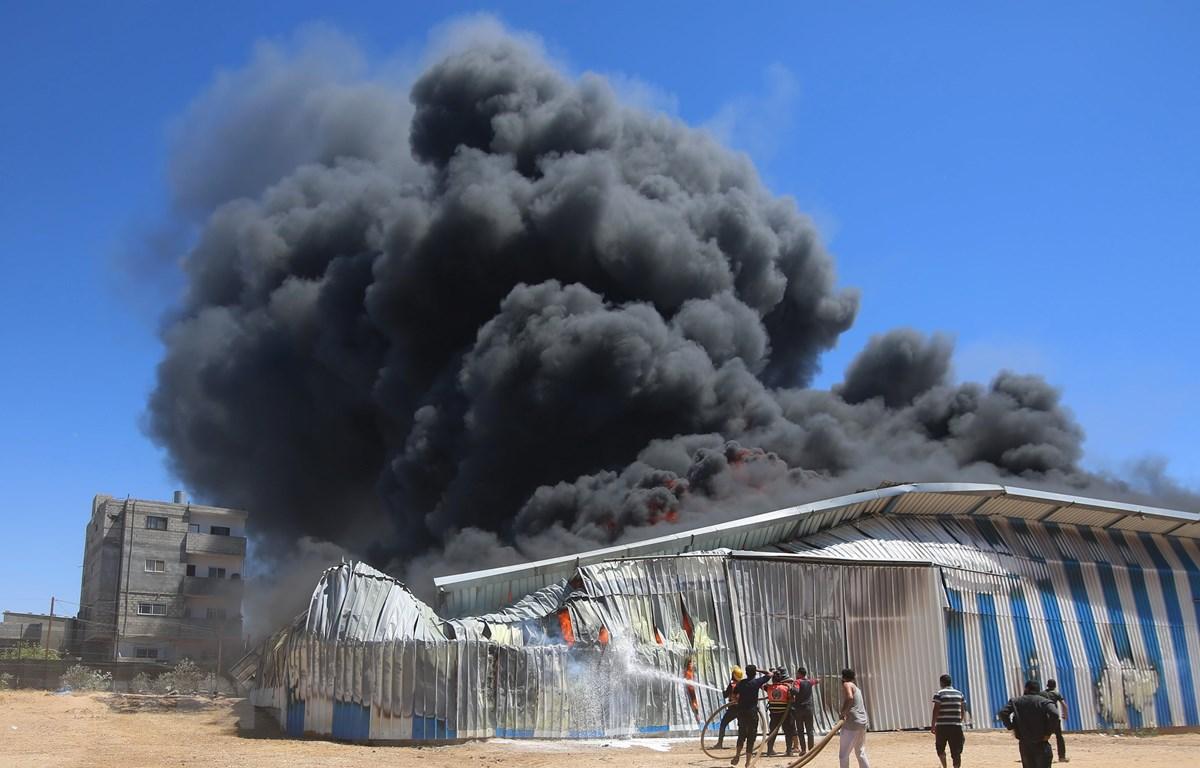 Lính cứu hoả nỗ lực dập lửa căn nhà bị trúng oanh kích của máy bay Israel tại thành phố Rafah, Dải Gaza ngày 18/5/2021. (Ảnh: THX/TTXVN)