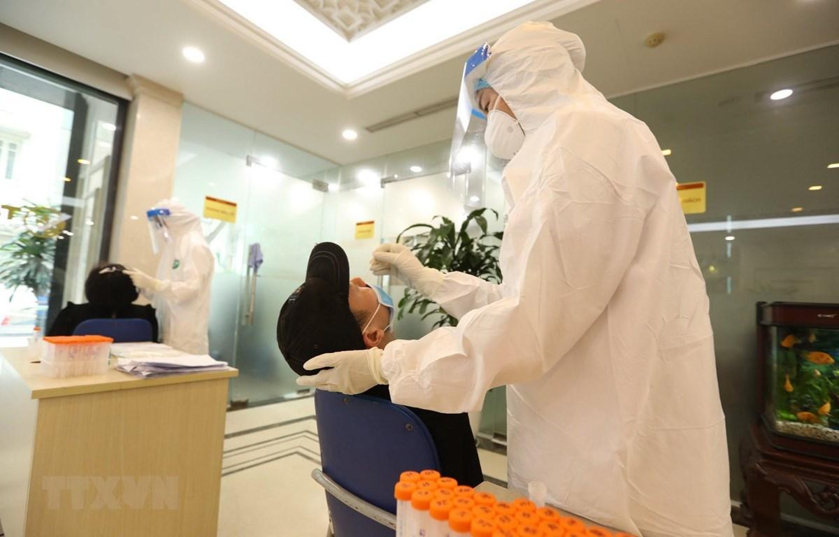 Nhân viên y tế lấy mẫu xét nghiệm. (Ảnh: Minh Quyết/TTXVN)