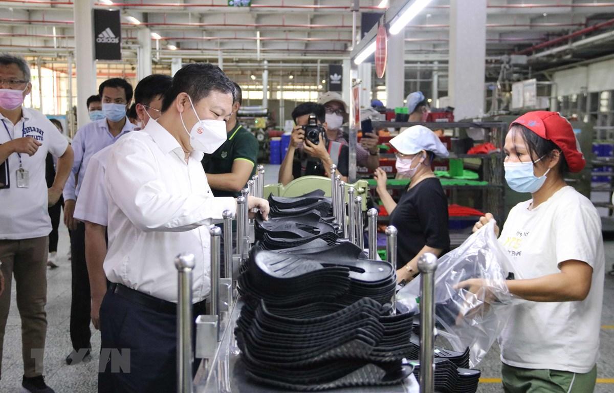 Phó Chủ tịch Dương Anh Đức thăm hỏi công nhân tại các chuyền sản xuất của Công ty trách nhiệm hữu hạn Pouyuen Việt Nam (quận Bình Tân). (Ảnh: Thanh Vũ/TTXVN)