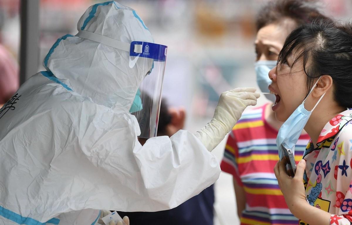 Nhân viên y tế lấy mẫu xét nghiệm COVID-19 cho người dân tại Quảng Châu, tỉnh Quảng Đông, Trung Quốc. (Ảnh: THX/TTXVN)