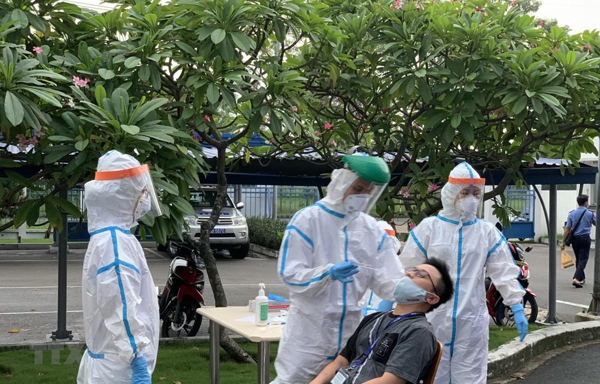 Các y bác sỹ Trung tâm kiểm soát bệnh tật Tp Hồ Chí Minh và Quận 7 thực hiện xét nghiệm. (Ảnh: Thanh Vũ/TTXVN)