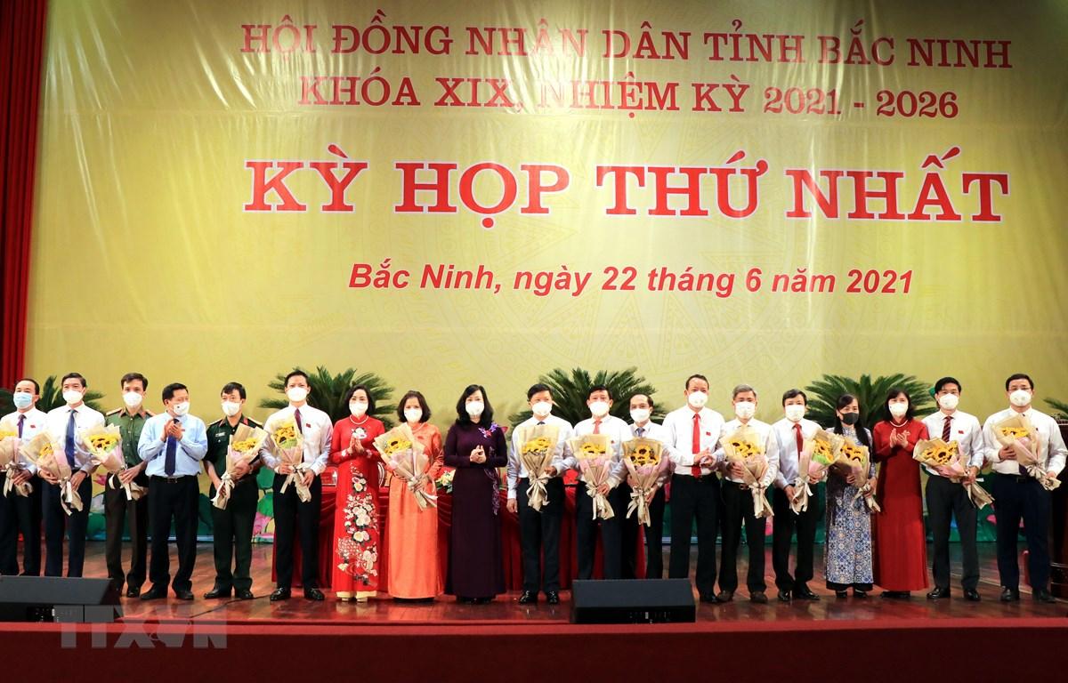 Lãnh đạo tỉnh Bắc Ninh tặng hoa các đồng chí được bầu giữ các chức danh chủ chốt của UBND tỉnh khóa XIX. (Ảnh: Đinh Văn Nhiều/TTXVN)