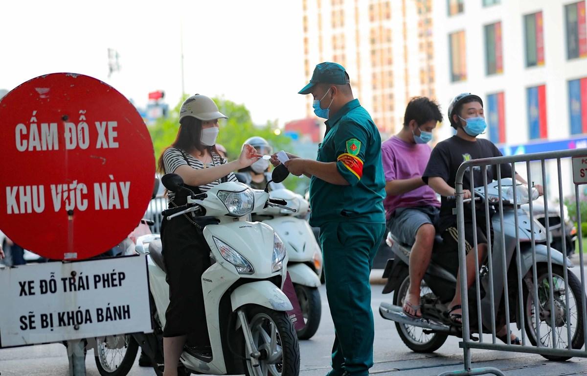 Các chốt kiểm soát của Ban chỉ đạo phòng chống dịch phường Vĩnh Tuy kiếm tra giấy tờ, thông tin của người ra, vào trên địa bàn. (Ảnh: Thanh Tùng/TTXVN)