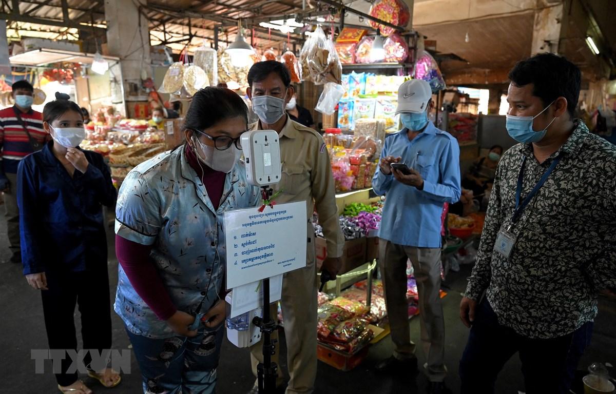 Người dân kiểm tra thân nhiệt trước khi vào chợ để phòng chống dịch COVID-19 tại Phnom Penh, Campuchia. (Ảnh: AFP/TTXVN)