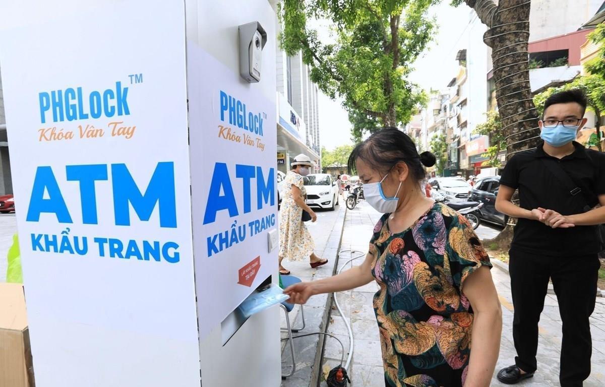 Người dân đến nhận khẩu trang từ cây ATM phát khẩu trang miễn phí trên phố Lạc Trung, Hà Nội. (Ảnh: Thành Đạt/TTXVN)