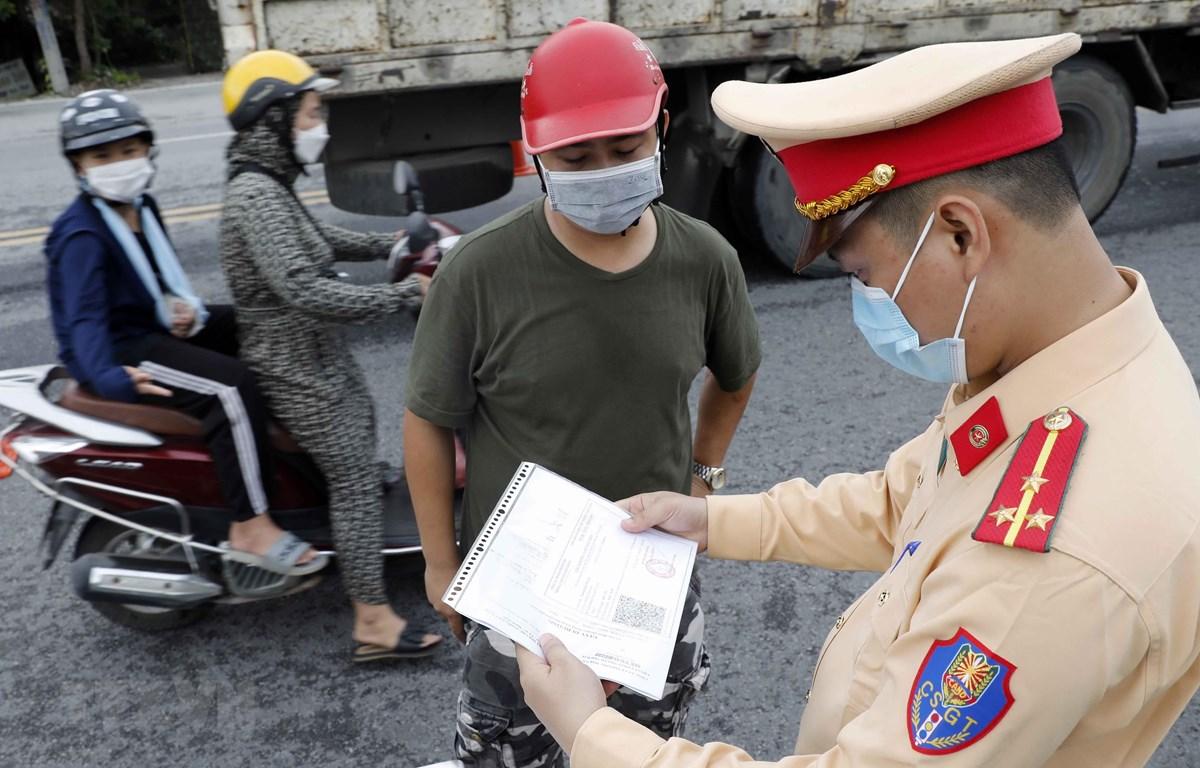 Cảnh sát giao thông kiểm tra giấy đi đường. (Ảnh: Trần Việt/TTXVN)
