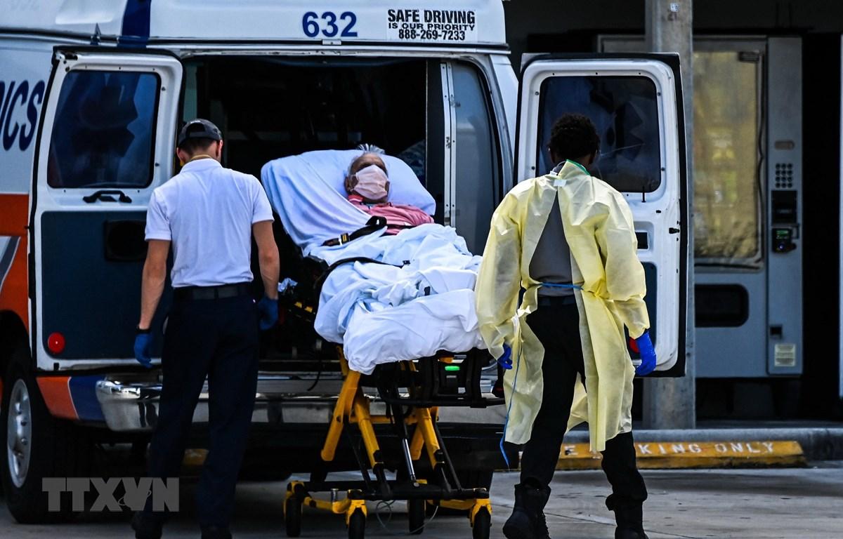 Nhân viên y tế chuyển bệnh nhân COVID-19 tới bệnh viện tại Miami, Mỹ. (Ảnh: AFP/TTXVN)