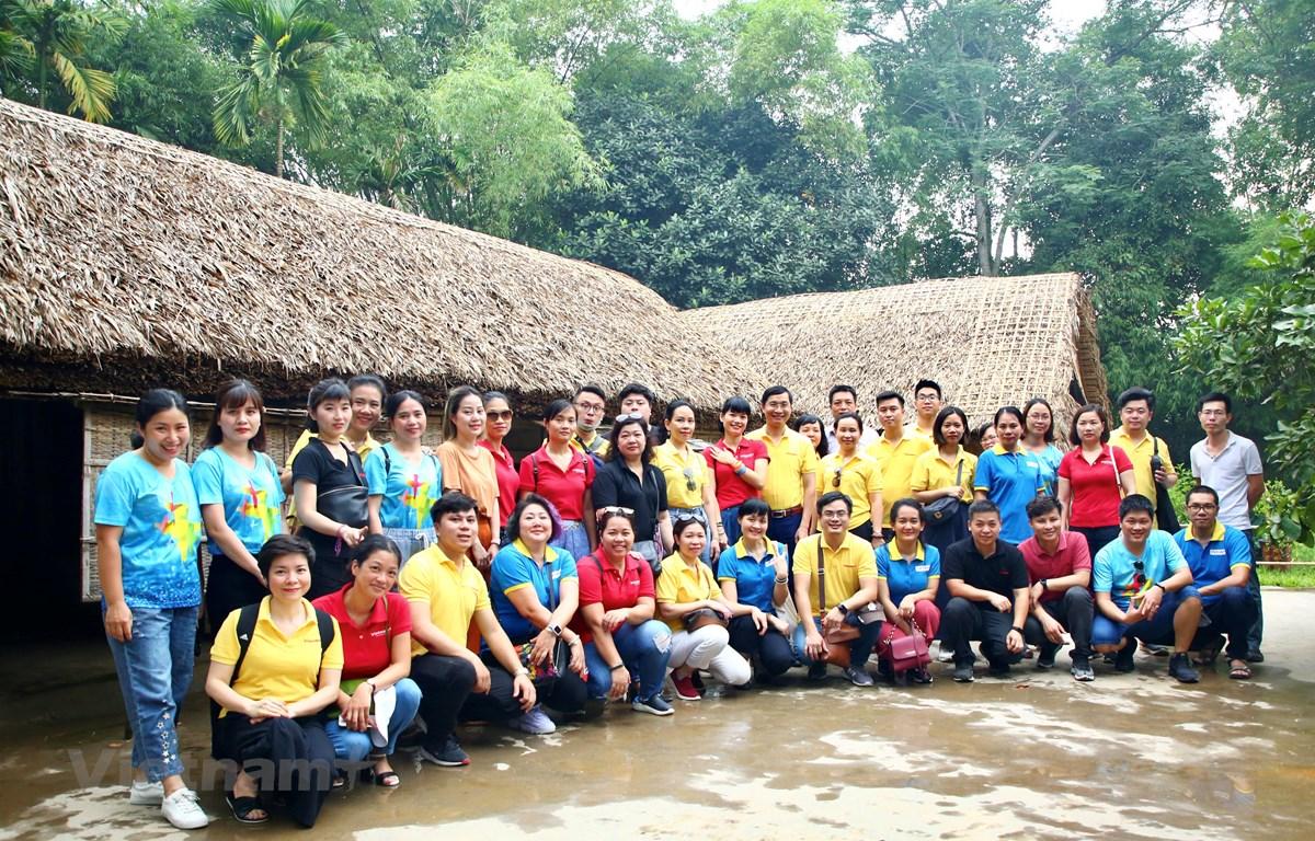 Tập thể ban lãnh đạo và cán bộ nhân viên Báo điện tử VietnamPlus chụp ảnh lưu niệm trước ngôi nhà của cụ Phó bảng Nguyễn Sinh Sắc ở làng Sen. (Ảnh: Nguyễn An/Vietnam+)