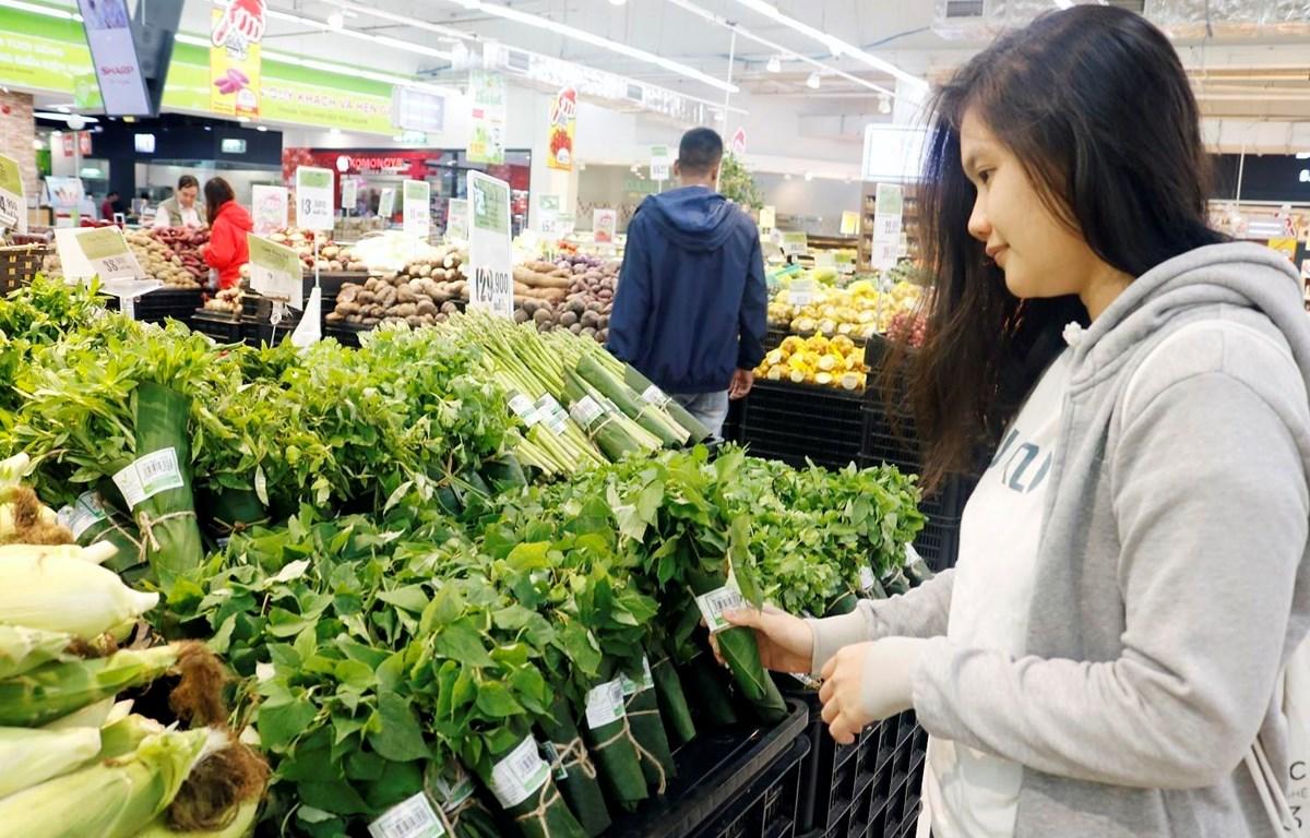 Nhiều siêu thị đã cam kết sử dụng phương pháp bọc hàng hóa, sản phẩm bằng lá chuối thay thế dần túi nilon. (Ảnh: TTXVN phát)