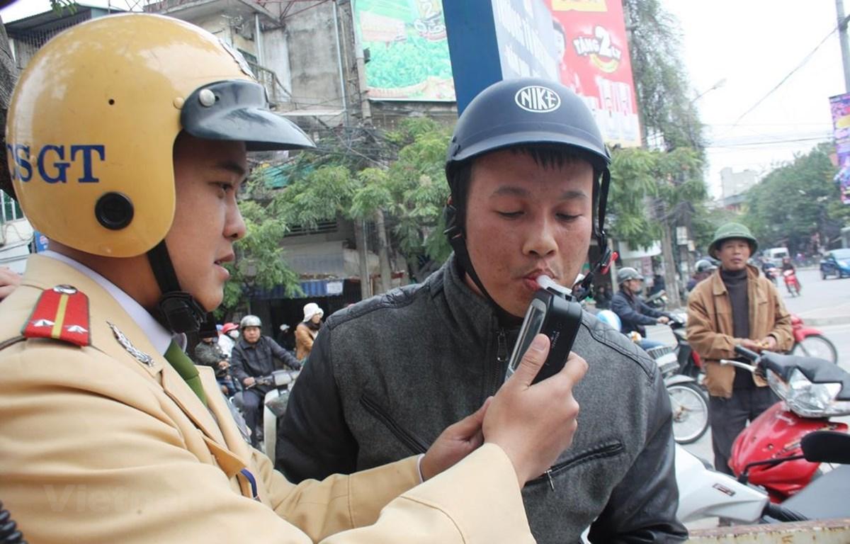 Cảnh sát giao thông tiến hành đo nồng độ cồn người điều khiển phương tiện xe cơ giới. (Ảnh: Việt Hùng/Vietnam+)