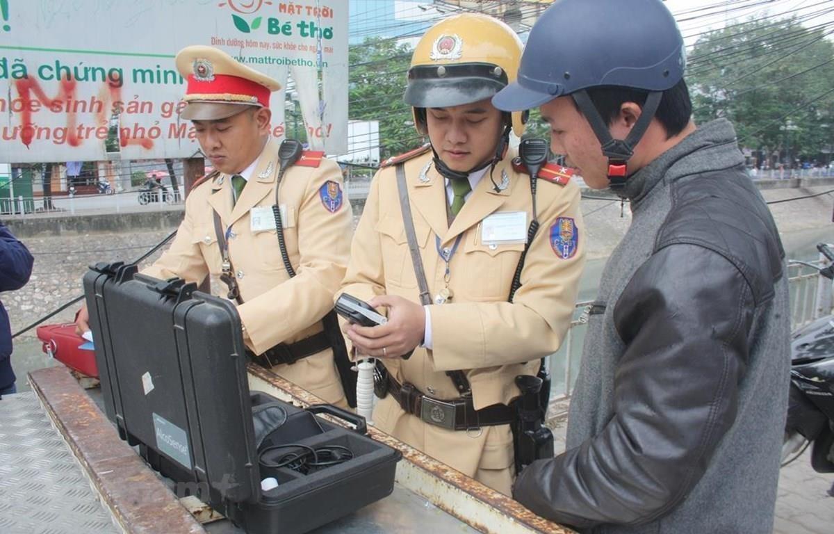 Cảnh sát giao thông tiến hành đo nồng độ cồn. (Ảnh: Việt Hùng/Vietnam+)