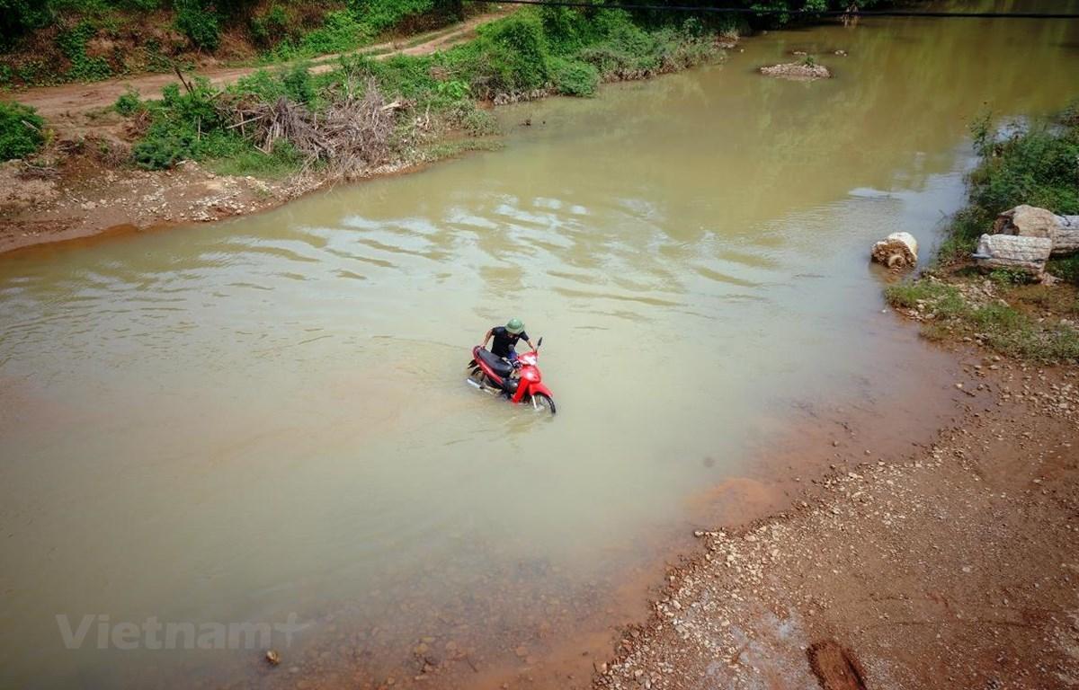 Người dân thôn Chằm Khon, xã Cấm Sơn, Lục Ngạn, tỉnh Bắc Giang vẫn phải dắt xe qua con sông vào mùa nóng khi chiếc cầu treo dân sinh đang được tiến hành xây dựng. (Ảnh: Việt Hùng/Vietnam+)