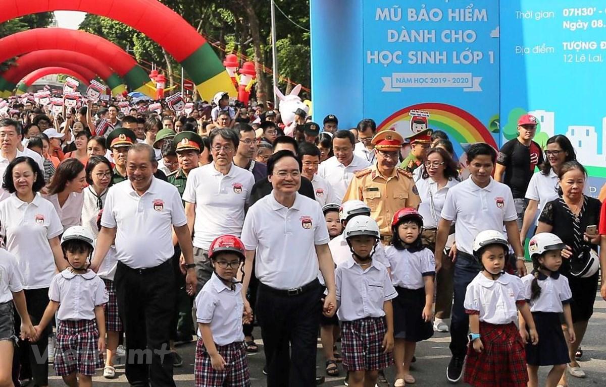 Lãnh đạo Chính phủ và các Bộ, ban ngành đi bộ kêu gọi toàn dân đội mũ bảo hiểm cho trẻ em khi tham giao giao thông. (Ảnh: Việt Hùng/Vietnam+)