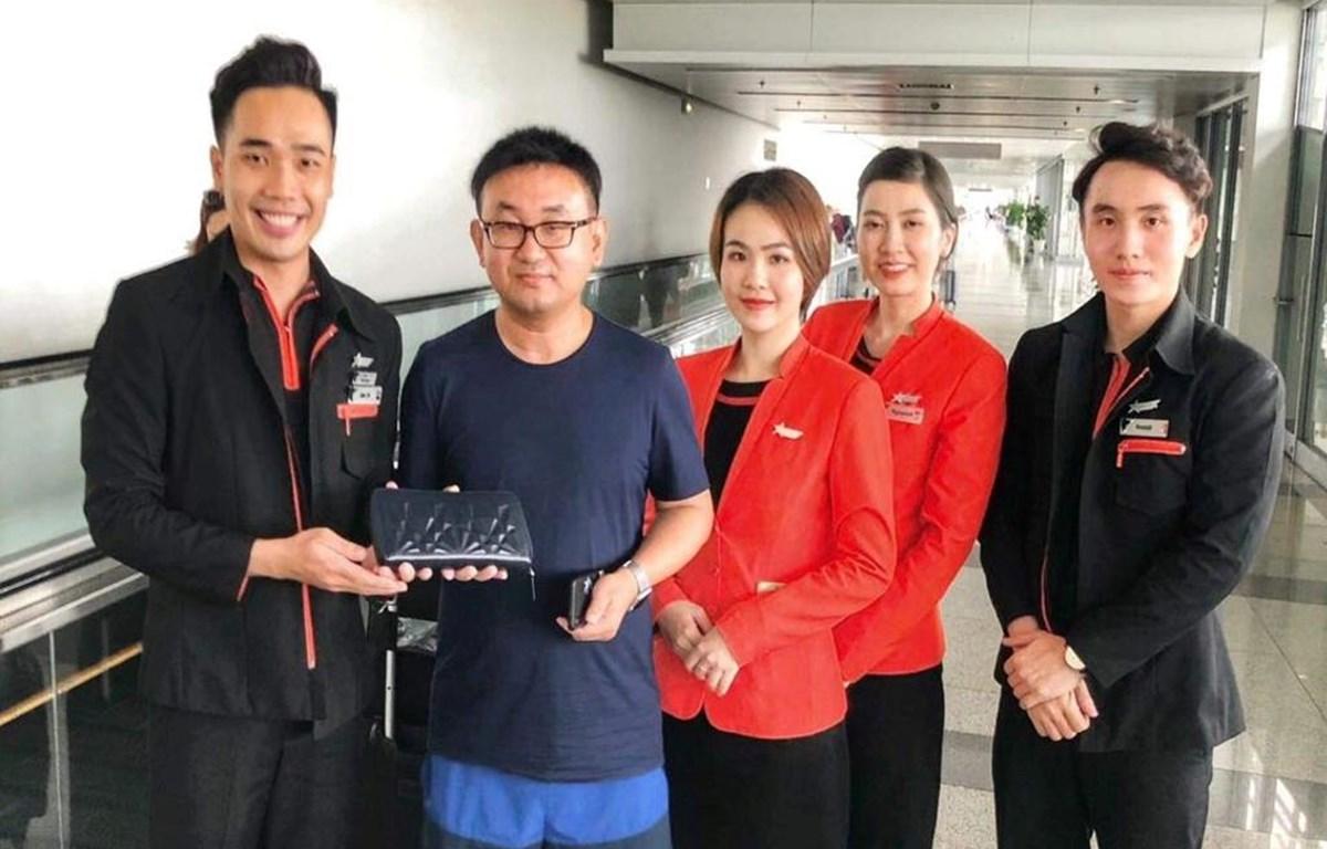 Tổ tiếp viên hãng hàng không Jetstar Pacific trao trả tài sản khách bỏ quên trên máy bay. (Ảnh: CTV/Vietnam+)