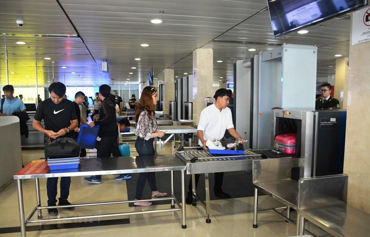 Hành khách làm thủ tục kiểm tra soi chiếu an ninh tại Cảng hàng không. (Ảnh: Việt Hùng/Vietnam+)
