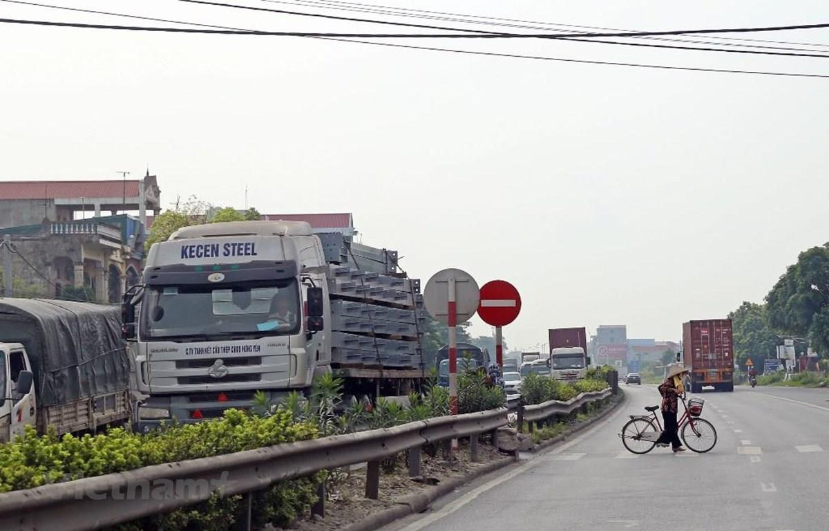 Lưu lượng xe đông, đường xuống cấp và hệ thống đường gom, cầu vượt chưa được thiết kế đầy đủ là những nguy hiểm rình rập với người đi trên Quốc lộ 5. (Ảnh: Huy Hùng/Vietnam+)