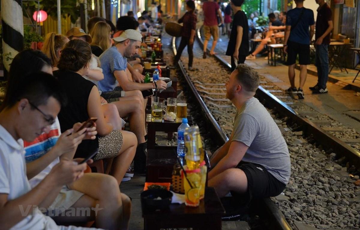 Trước khi bị đóng cửa, nhiều du khách đã đến Phố càphê đường tàu để trải nghiệm cảm giác ngồi uống nước sát với đoàn tàu chạy qua. (Ảnh: Hoàng Anh/Vietnam+)