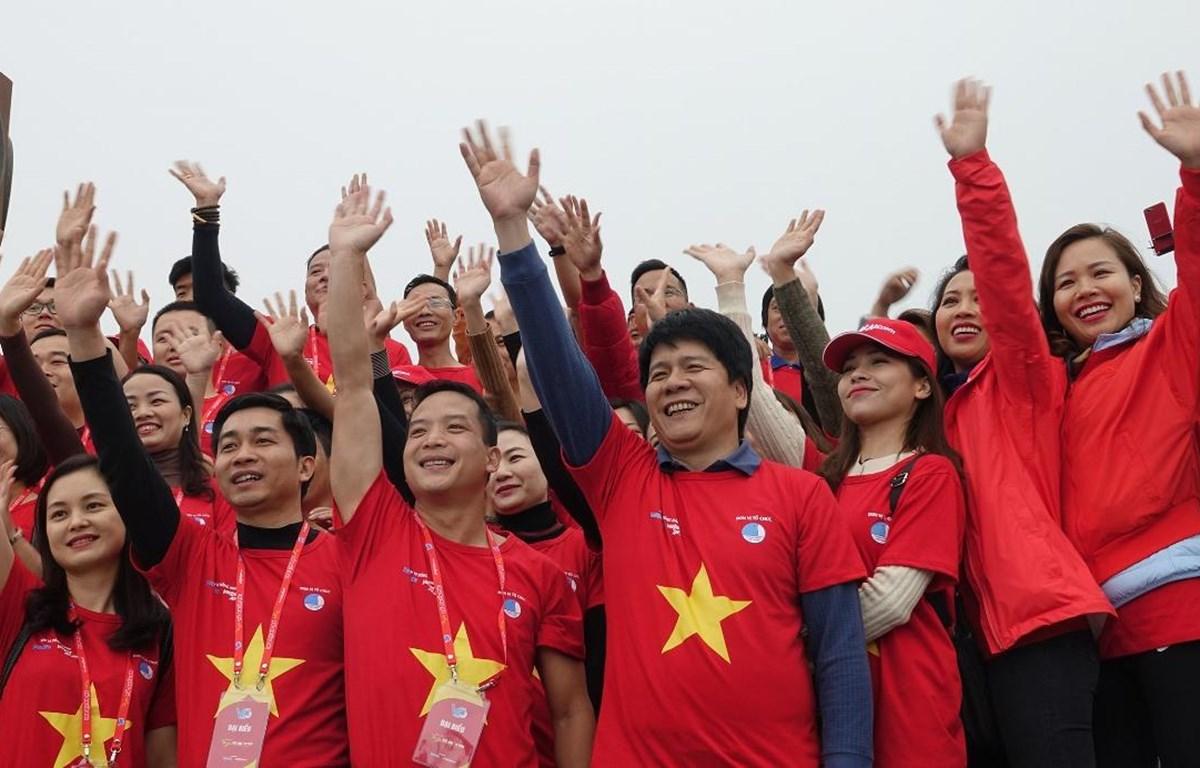 """Đoàn viên, thanh niên của Vietjet tham gia lễ công bố thông điệp Hành trình """"Tôi yêu Tổ quốc tôi"""" tại cột cờ Lũng Cũ. (Ảnh: CTV/Vietnam+)"""