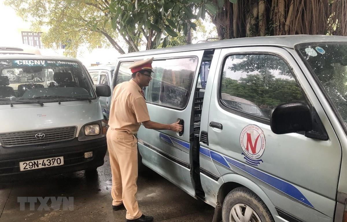 Cảnh sát giao thông kiểm tra một xe ôtô chở học sinh bị tạm giữ. (Ảnh: Đức Phương/TTXVN)