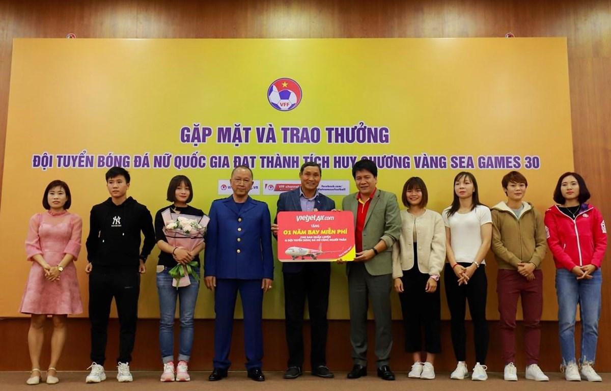 Ban huấn luyện các cầu thủ đội tuyển bóng đá nữ Việt Nam nhận phần quà 1 năm bay miễn phí từ hãng hàng không Vietjet. (Ảnh: CTV/Vietnam+)