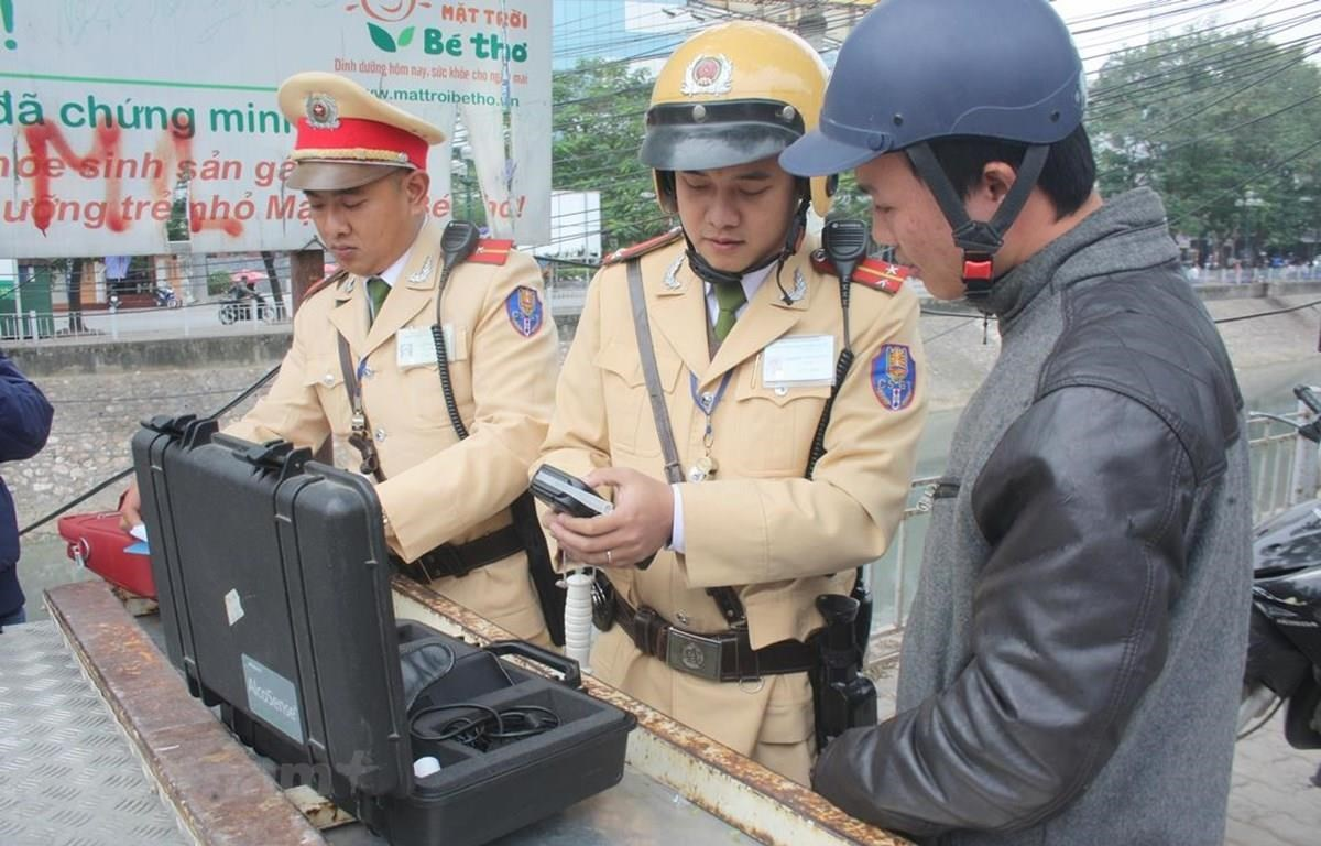 Cảnh sát giao thông tiến hành đo nồng độ cồn đối với người điều khiển phương tiện. (Ảnh: Việt Hùng/Vietnam+)
