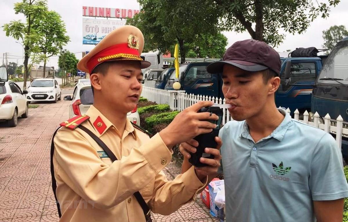Cảnh sát giao thông tiến hành kiểm tra đo nồng độ cồn đối với lái xe. (Ảnh: Việt Hùng/Vietnam+)