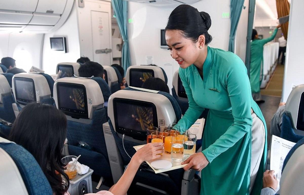 Tiếp viên phục vụ đồ uống trên chuyến bay của Vietnam Airlines. (Ảnh: CTV/Vietnam+)